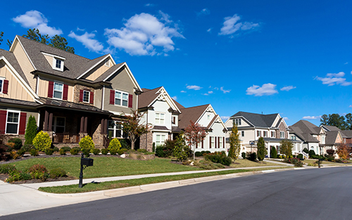 Street of large suburban homes on sunny day
